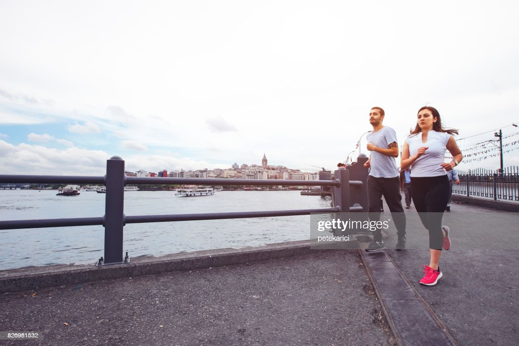 Young couple jogging in Istanbul, Galata Bridge : Stock Photo
