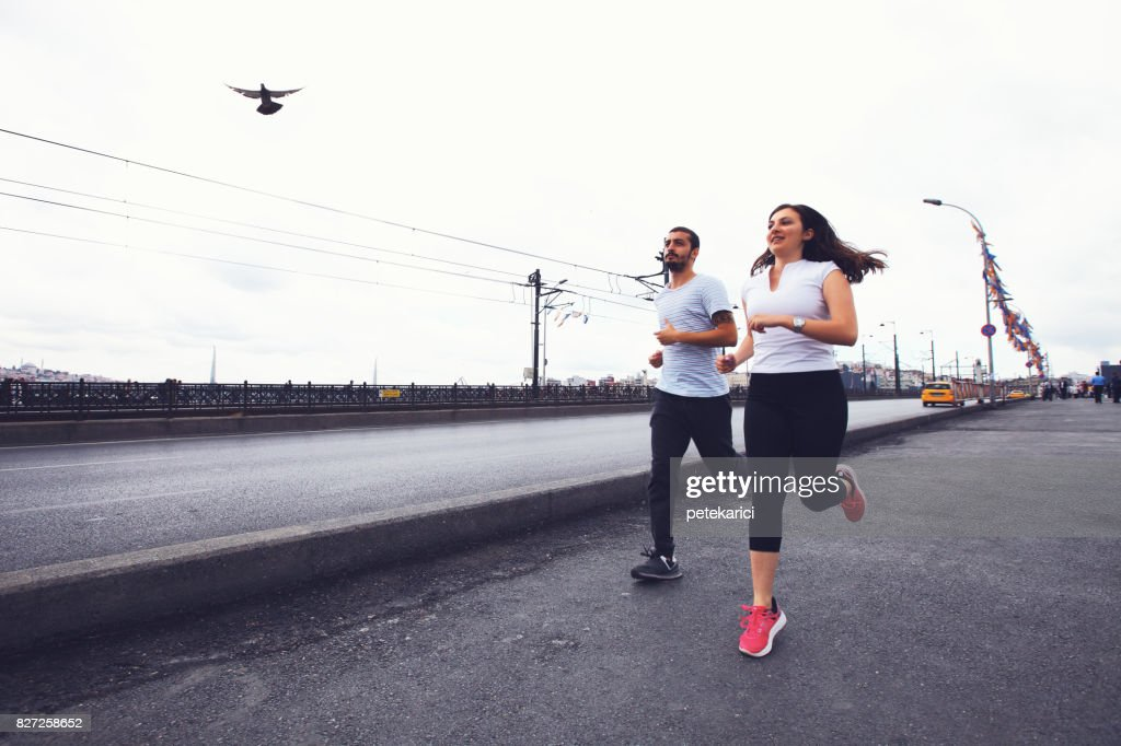 Young couple jogging in Istanbul, Galata Bridge : Stock Photo