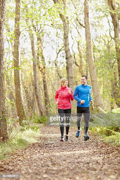 Young couple jogging through forest