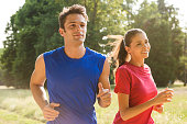 Healthy Young Couple Jogging In Bright Sunny Day.