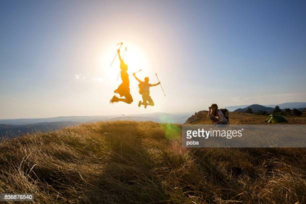 Young couple  jumping for joy on mountain peak
