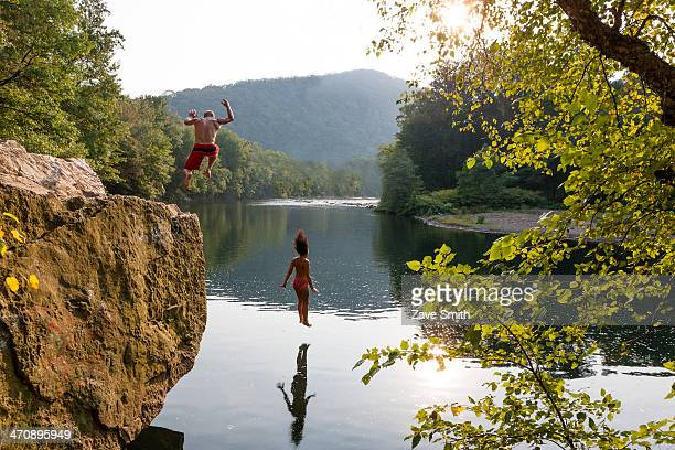 Young couple jumping from rock ledge, Hamburg, Pennsylvania, USA