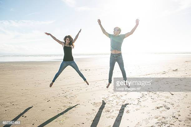 A young couple jumping in the sunshine on the beach at Porthmadog
