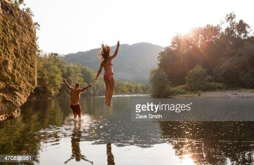 Young couple jumping into river, Hamburg, Pennsylvania, USA