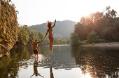 Young couple jumping into river, Hamburg, Pennsylvania, USA