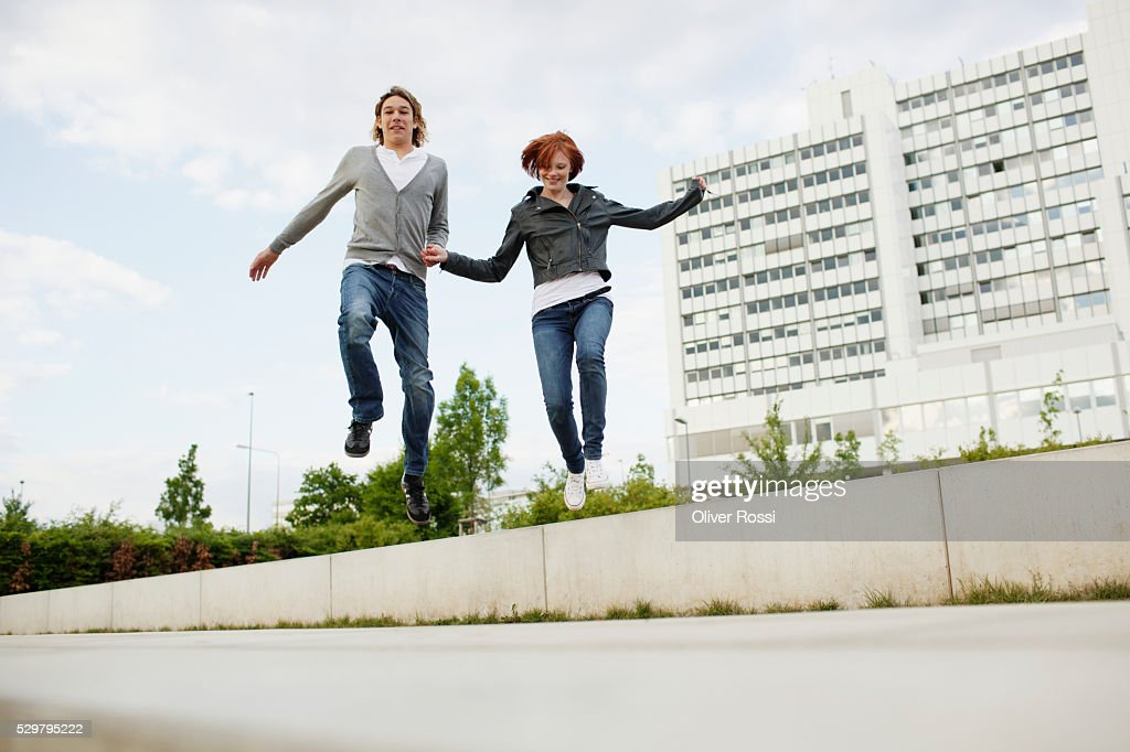 Young couple jumping off wall : Photo