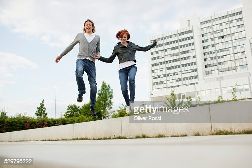 Young couple jumping off wall : Stock Photo