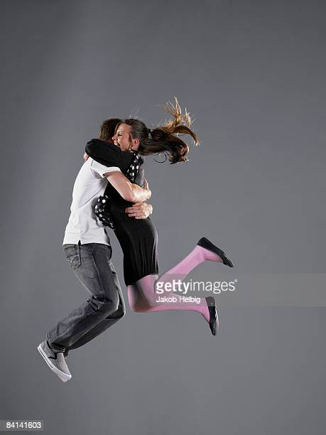Young couple jumping together, hugging