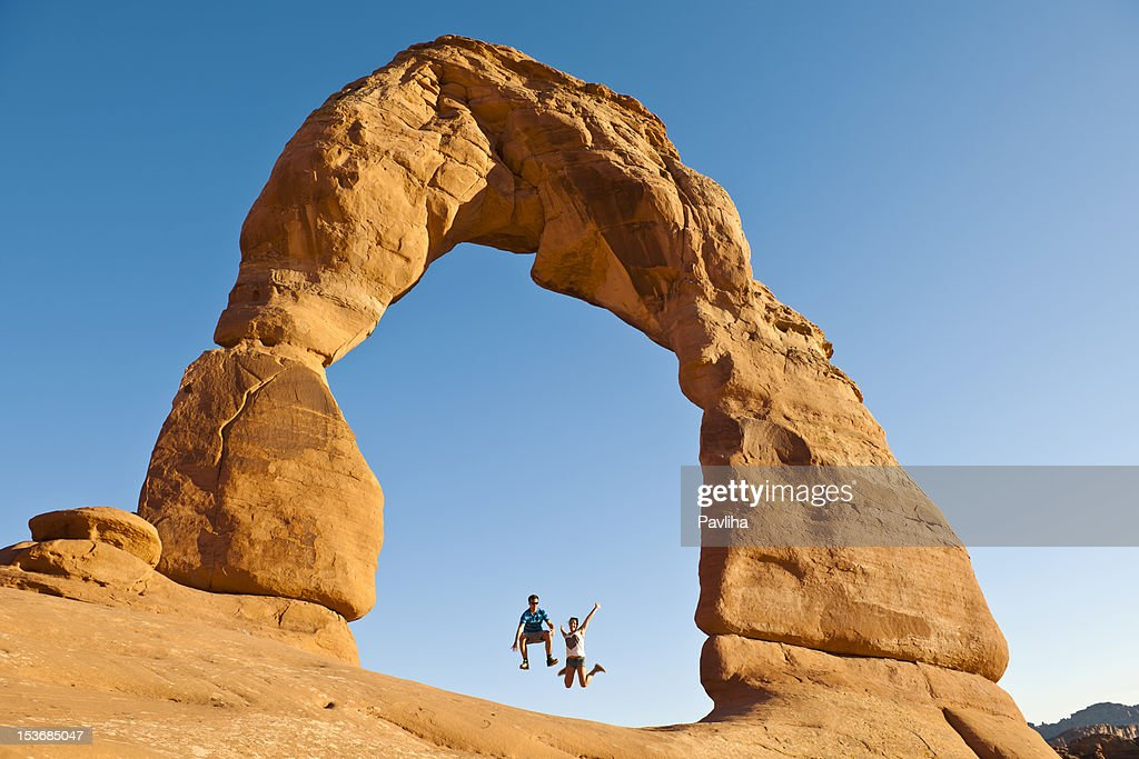 Young Couple Jumping under Delicate Arch Utah USA : Stock Photo