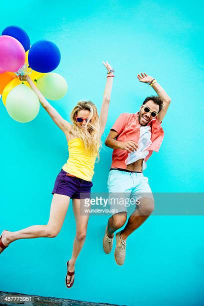 Young couple jumping with joy colorful balloons