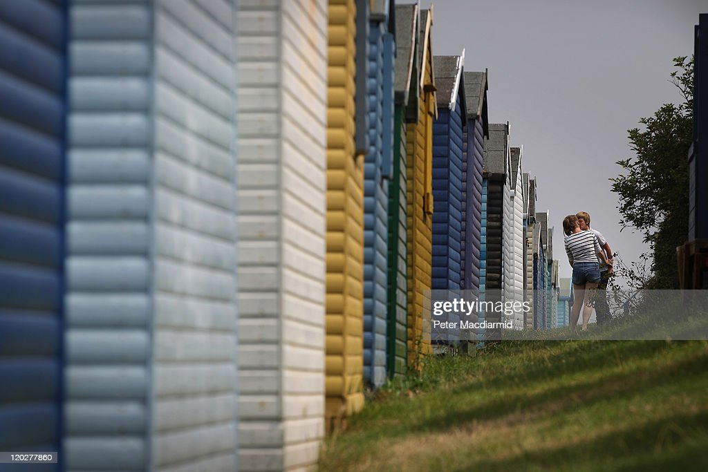 A young couple kiss behind a row of beach huts on August 3, 2011 in Whitstable, England. Parts of southern England are experiencing high summer temperatures.