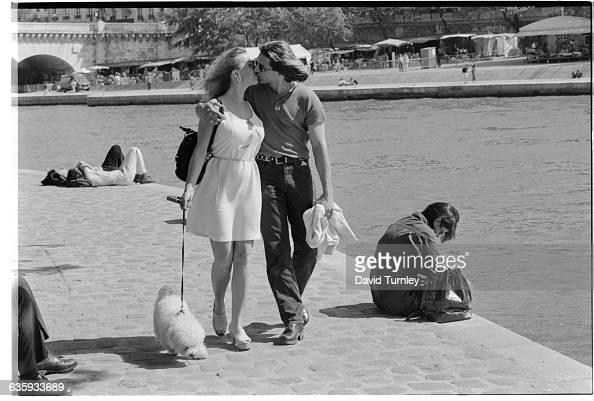 A young couple kisses as they strolls along the Seine with their dog