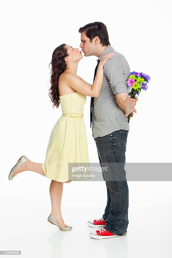 Young couple kissing against white background : Stock Photo