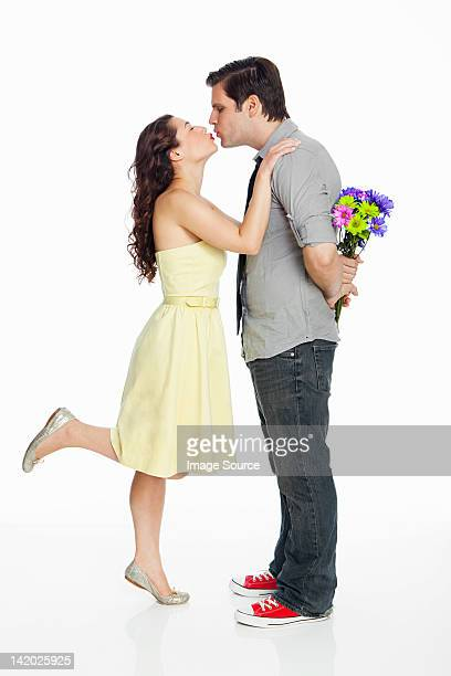 Young couple kissing against white background