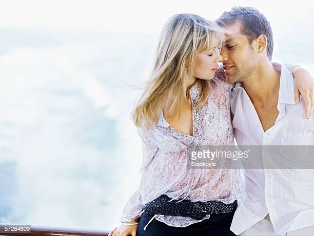 Young couple kissing and standing on a motor boat