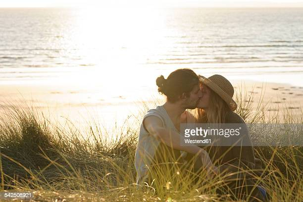 Young couple kissing at beach dunes in front of Atlantic