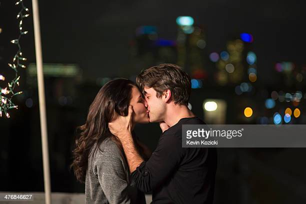 Young couple kissing at rooftop party