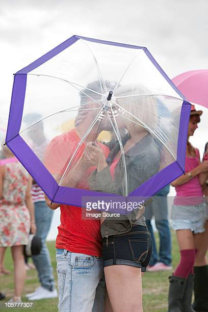 Young couple kissing behind umbrella at festival