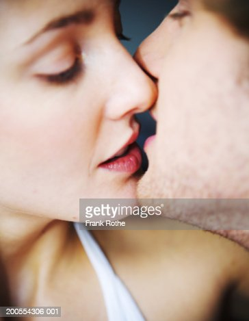 Young couple kissing, close-up : Stock Photo