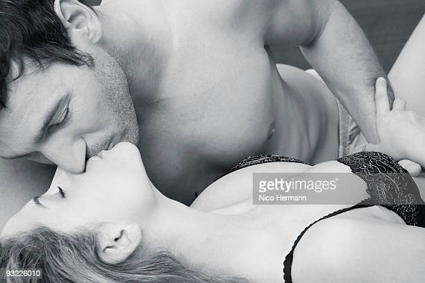 Couple kissing in bed, close-up