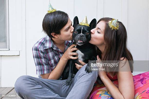 Young couple kissing dog on cheek and wearing party hats