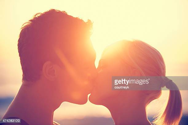 Young couple kissing each other at sunset.