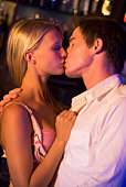 Young couple kissing in a bar