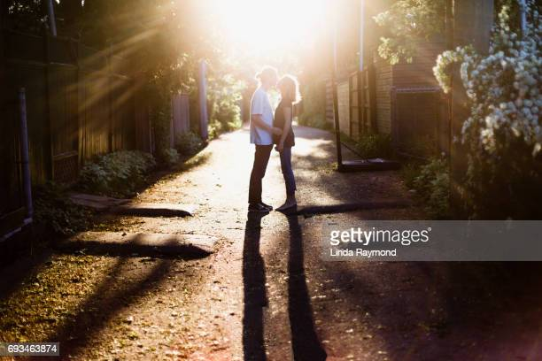 A young couple kissing in an alley at sunset