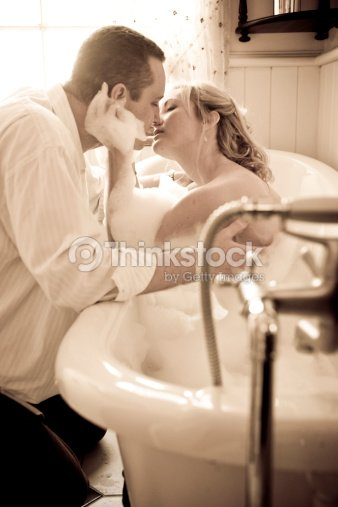 young couple kissing in bathroom with vintage bathtub stock photo