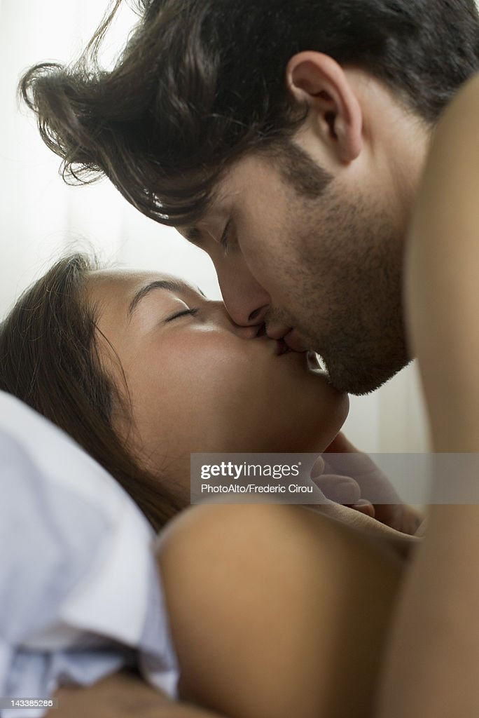 Young couple kissing in bed : Stock Photo