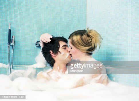 young couple kissing in bubble bath stock photo getty images
