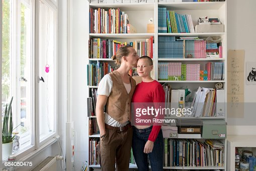 Young couple kissing in front of bookshelf at home