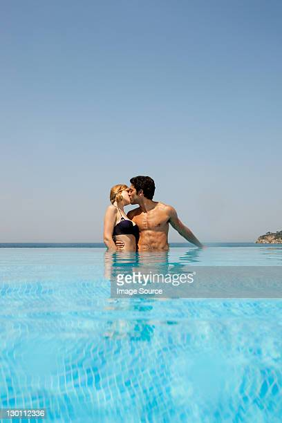 Young couple kissing in infinity pool