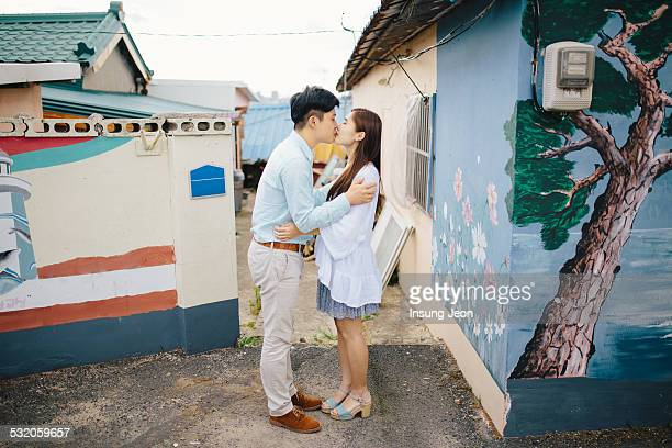 Young couple kissing in old alleyway