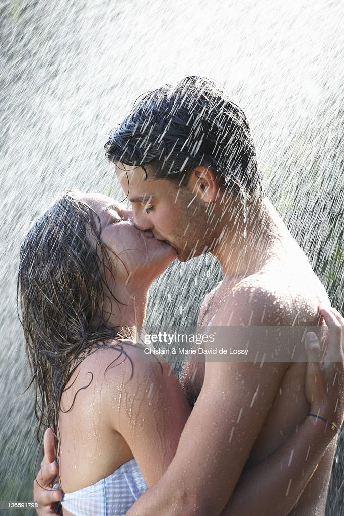 Young couple kissing in rain : Stock Photo