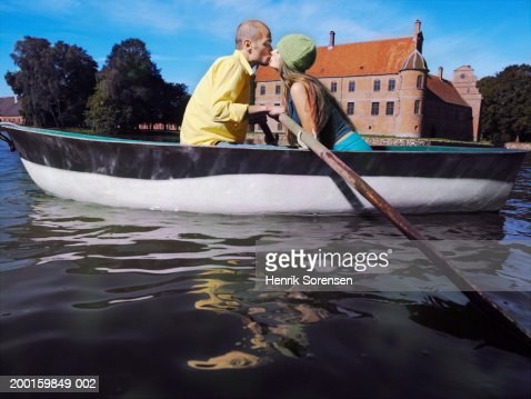 Young couple kissing in rowing boat on lake, side view : Bildbanksbilder