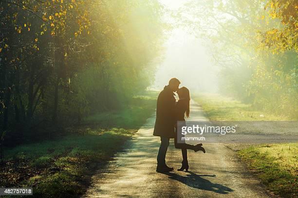 若いカップルのキス太陽の