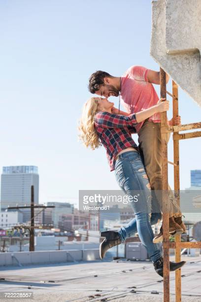 Young couple kissing on a fire escape on a roof