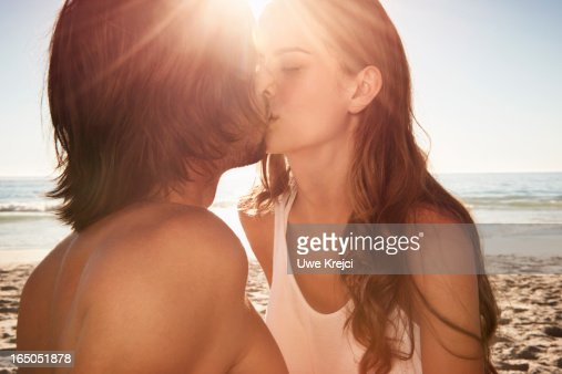 Young couple kissing on beach at sunset
