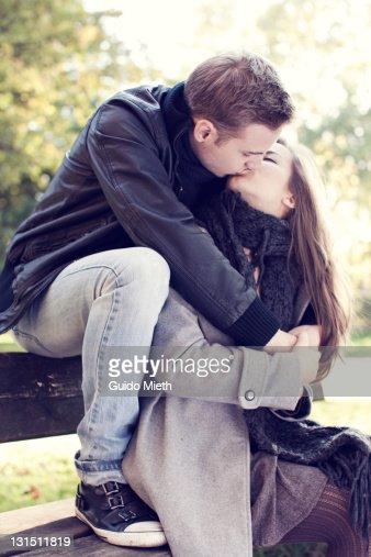 Young couple kissing on park bench in autumn. : Stock Photo
