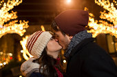 Young couple kissing on street at christmas