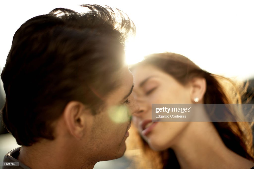 Young couple kissing, outdoors, close-up : Stock Photo