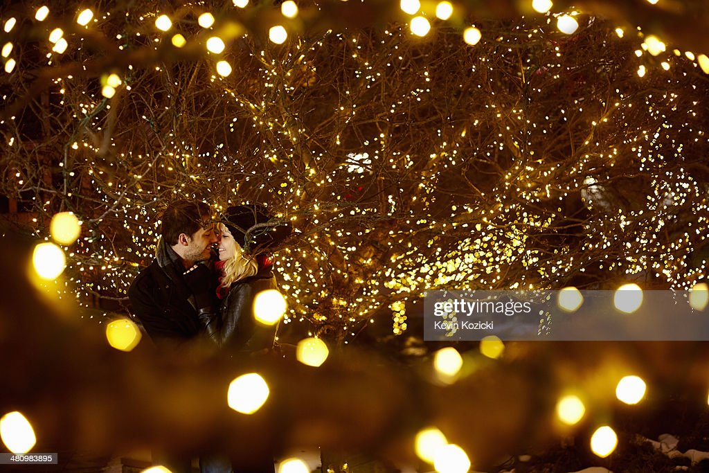 Young couple kissing surrounded by city xmas lights