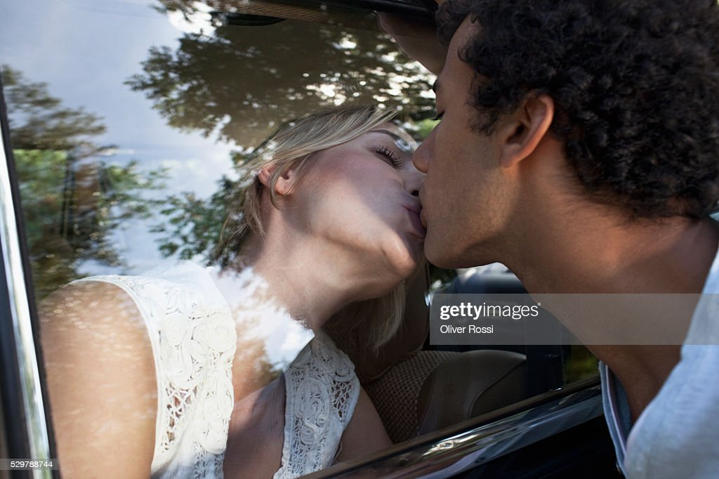 Young couple kissing through a car window : Stockfoto