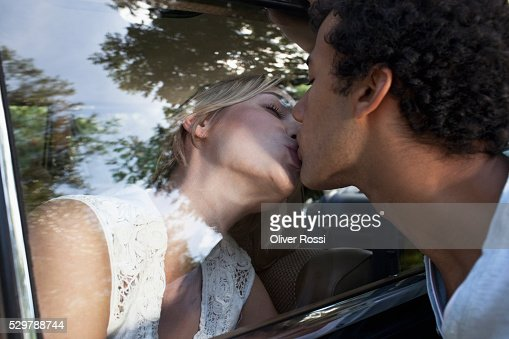 Young couple kissing through a car window : Stock-Foto