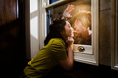 Young couple kissing together through glass window
