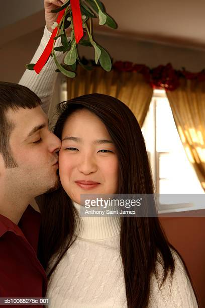Young couple kissing under mistletoe, smiling, close-up