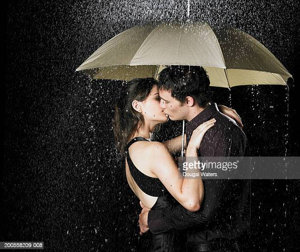 Young couple kissing under umbrella in rain at night, side view