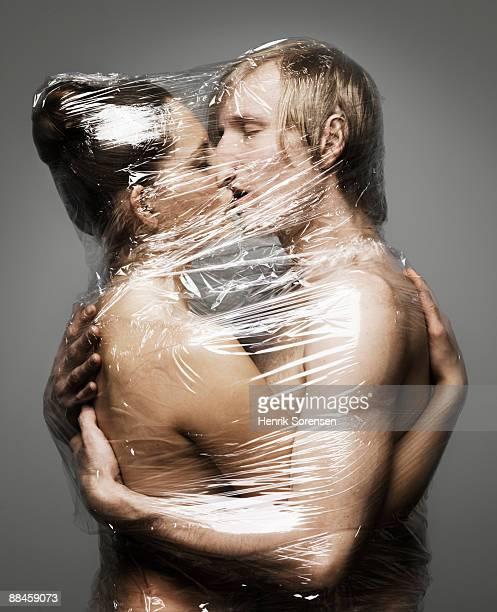 Young couple kissing - wrapped up with plastic