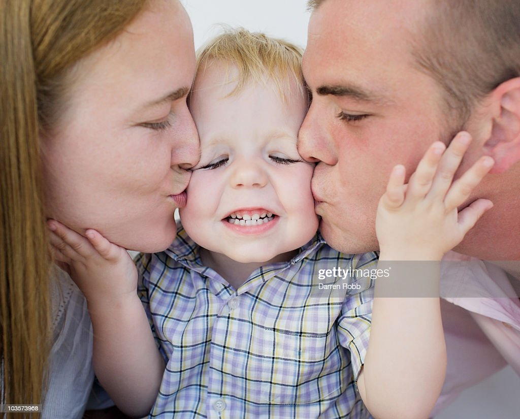 Young couple kissing young boy : Stock Photo